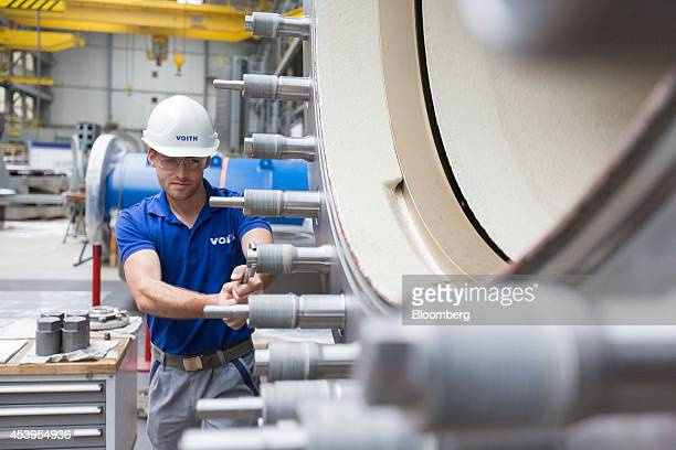 An employee tightens bolts on a Voith spherical valve for a hydropower plant in the workshop at the Voith GmbH factory in Heidenheim Germany on...