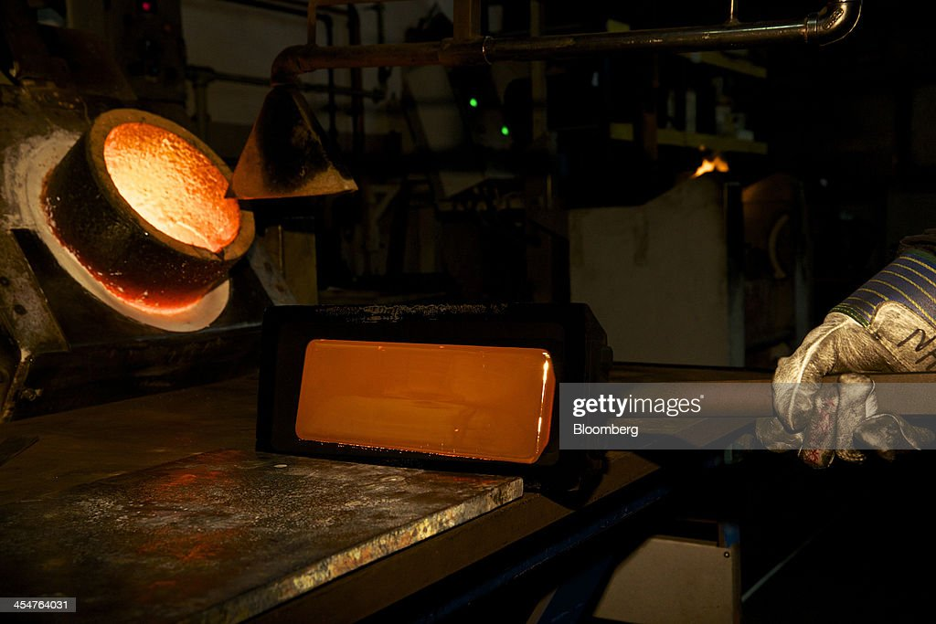 An employee tips a freshly cast 400 ounce gold bar onto a workbench after casting at a precious metal refinery near Mendrisio Switzerland on Thursday...