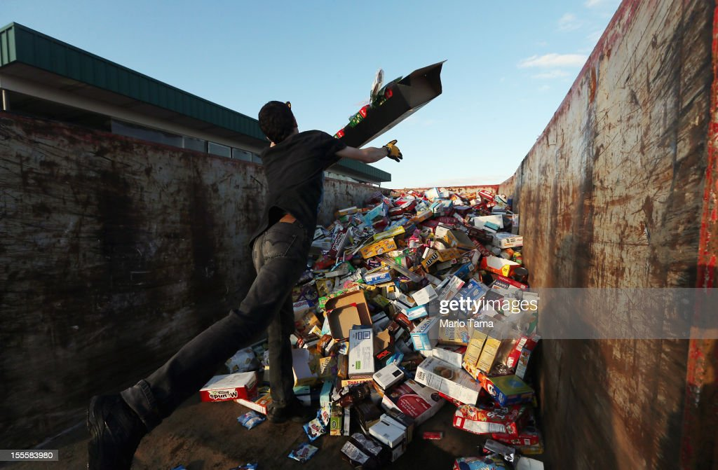 An employee tossed out damaged goods from an Acme supermarket into a dumpster following Superstorm Sandy on November 5, 2012 in Long Beach Township, New Jersey. Employees volunteered to perform the task of cleaning out the store. Today was the first day residents were allowed to return to Long Beach Island following the storm.