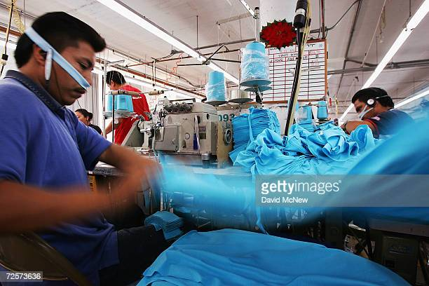 An employee tosses a garment onto a stack after sewing his portion of it at the American Apparel garment factory on December 14 2004 in Los Angeles...