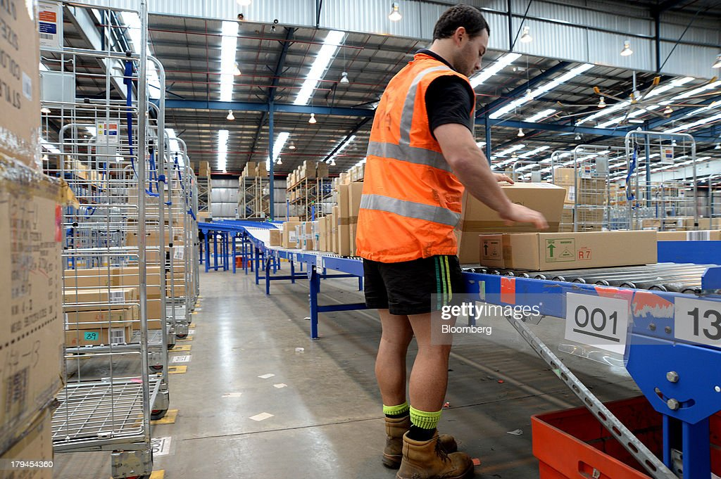 An employee transfers boxes of merchandise from a conveyor onto trolleys at the Myer Holdings Ltd. distribution center in Melbourne, Australia, on Tuesday, Sept. 3, 2013. A Bureau of Statistics report released in Sydney on Sept. 4 showed household spending climbed 0.4 percent in the second quarter, adding 0.2 percentage point to gross domestic product growth. Photographer: Carla Gottgens/Bloomberg via Getty Images