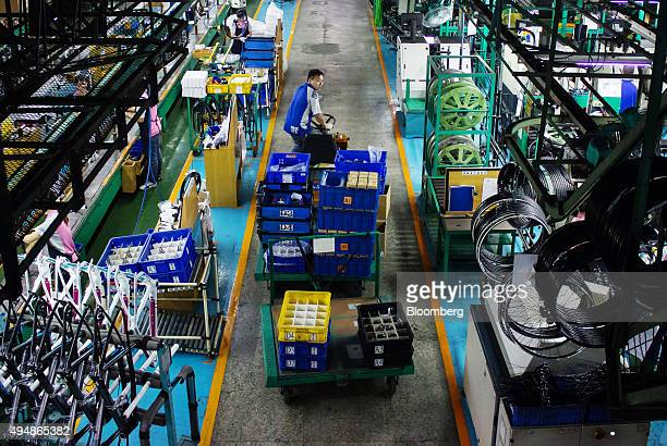 An employee transports bicycle parts on the assembly line of the Giant Manufacturing Co bicycle manufacturing facility in Taichung Taiwan on Thursday...