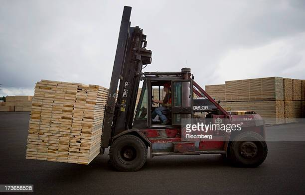 An employee transports cut lumber at the West Fraser Timber Co sawmill in Quesnel British Columbia Canada on Thursday July 11 2013 West Fraser Timber...
