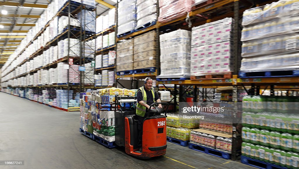 An employee transports produce with a pallet truck inside WM Morrison Supermarkets Plc's distribution center in Wakefield, U.K., on Thursday, Nov. 22, 2012. Britain's economy will return to growth next year after stagnating in 2012, with expansion weighted in the second half, according to Bank of England projections published yesterday. Photographer: Simon Dawson/Bloomberg via Getty Images