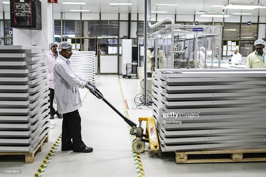 An employee transports solar panel aluminum frames on the solar photovoltaic module production line at the Tata Power Solar Systems Ltd. manufacturing plant in Bangalore, India, on Tuesday, June 11, 2013. Tata Groups solar unit is expanding its business building plants for customers, forecasting that offices and factories will be paying more for grid power than solar by 2016 in most Indian states. Photographer: Dhiraj Singh/Bloomberg via Getty Images