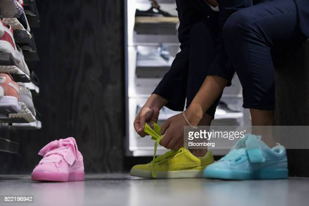 An employee tries on women's trainers inside a Puma SE sportswear clothing store in Berlin Germany on Tuesday July 25 2017 Puma increased its...