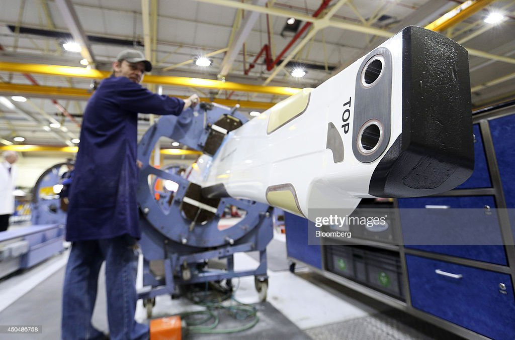 An employee turns a clamp holding a blade for a helicopter produced by AgustaWestland, a unit of Finmeccanica SpA, at the company's plant in Yeovil, U.K., on Thursday, June 12, 2014. U.K. unemployment declined more than expected and industrial production rose at the fastest annual pace since 2011, according to reports released this week. Photographer: Chris Ratcliffe/Bloomberg via Getty Images
