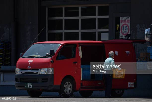 An employee unloads a crate from a Japan Post Co truck at a post office in Kawasaki Kanagawa Japan on Tuesday April 25 2017 Japan Post Holdings Co...