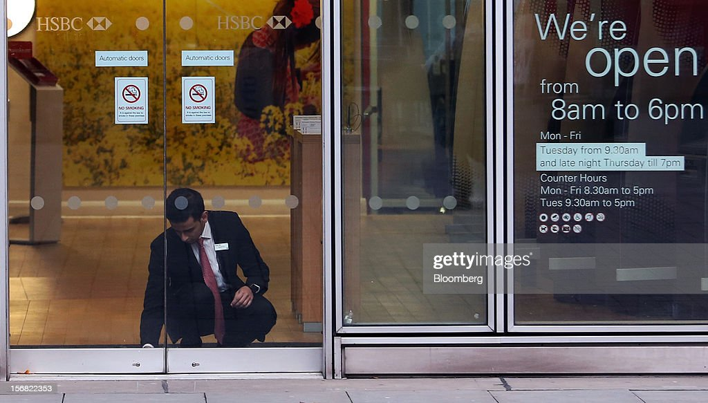 An employee unlocks bolts on the front doors of a HSBC Holdings Plc bank branch ahead of opening in London, U.K., on Thursday, Nov. 22, 2012. Shares of HSBC have climbed 26 percent this year in London trading, and 30 percent in Hong Kong, as Chief Executive Officer Stuart Gulliver pared costs and sold assets to revive profit and focus on emerging economies in which the bank has a greater market share. Photographer: Chris Ratcliffe/Bloomberg via Getty Images