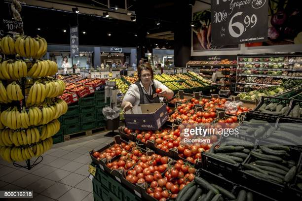 An employee unpacks tomatoes into the fresh produce aisle inside a Super Konzum supermarket operated by Agrokor dd in Zagreb Croatia on Tuesday June...