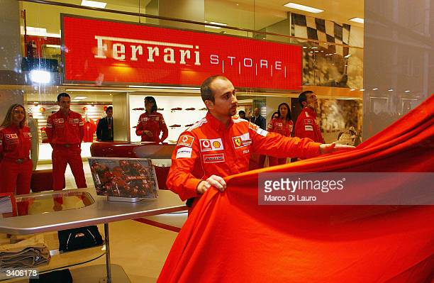 An employee unveils the window of the Ferrari Store during the opening ceremony on April 16 2004 in Rome Italy German Formula One World Champion...