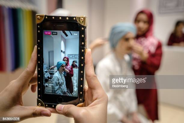 An employee updates an Instagram Inc live feed during a styling session at the FashionValet Sdn store in Kuala Lumpur Malaysia on Tuesday June 20...