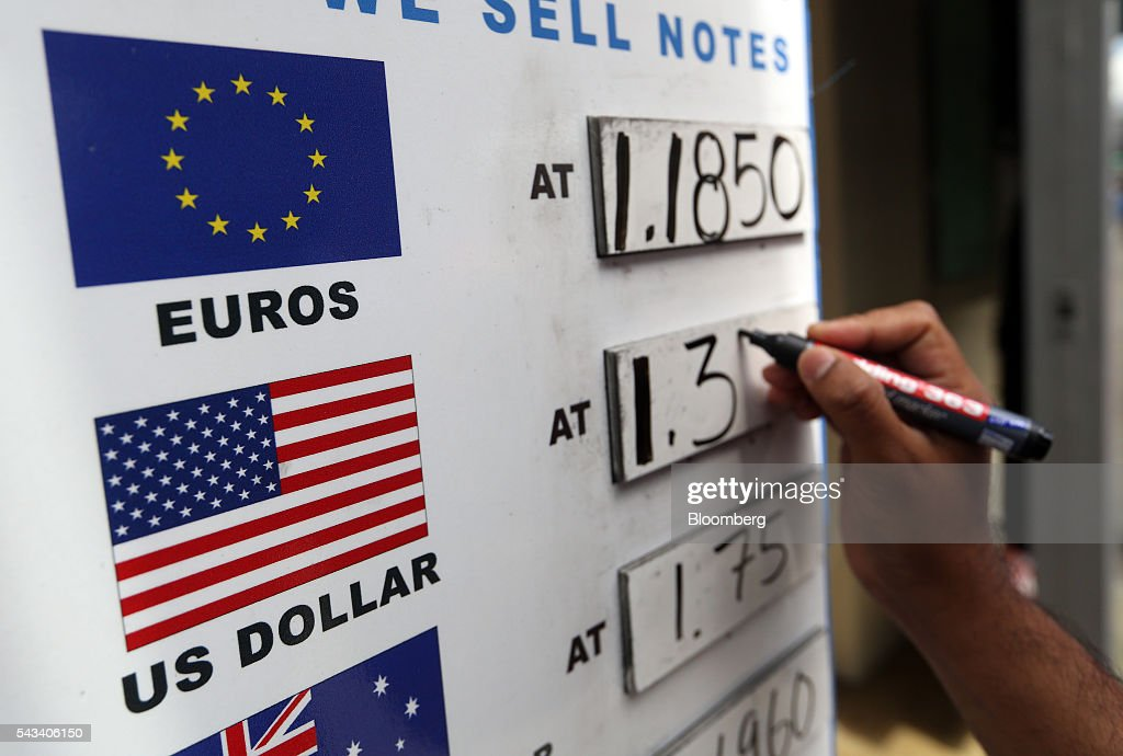An employee updates exchange rates on a board outside outside a foreign currency exchange bureau in London, U.K., on Tuesday, June 28, 2016. The pound rose for the first time since the U.K.s vote to leave the European Union, as a recovery in investor appetite for higher-yielding assets seeped through currency markets. Photographer: Chris Ratcliffe/Bloomberg via Getty Images