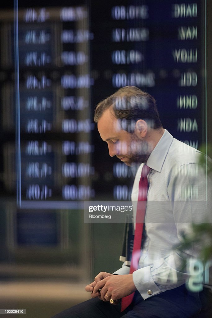 An employee use his mobile device near a display of share price information inside the London Stock Exchange Group Plc's (LSE) headquarters in London, U.K., on Monday, March 11, 2013. European stocks fell from a 4 1/2-year high as Fitch Ratings downgraded Italy and China's retail sales and industrial output missed forecasts. Photographer: Jason Alden/Bloomberg via Getty Images