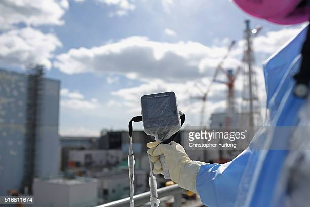 An employee uses a a radiation dosage monitor as workers continue the decontamination and reconstruction process at the Tokyo Electric Power Co's...