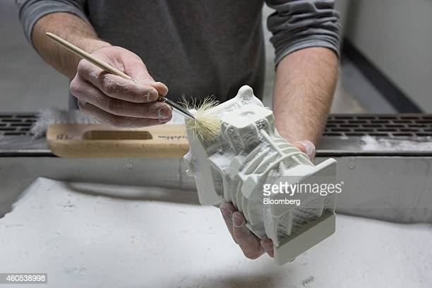 An employee uses a brush to remove mold sand from a 2stroke automobile engine during automotive part manufacture at the Voxeljet AG 3D printing plant...