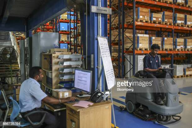 An employee uses a computer as a colleague operates a rideon vacuum sweeper at a warehouse inside the Grundfos AS factory in Chennai India on Monday...