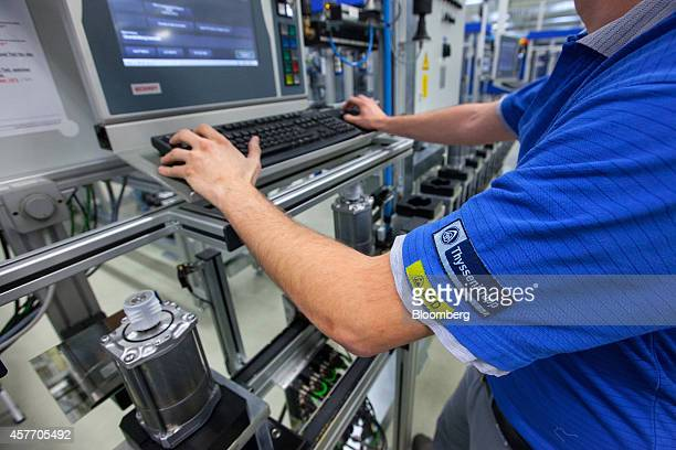 An employee uses a computer keyboard on the electronic automotive steering systems power pack production line at ThyssenKrupp AG's Presta SteerTec...