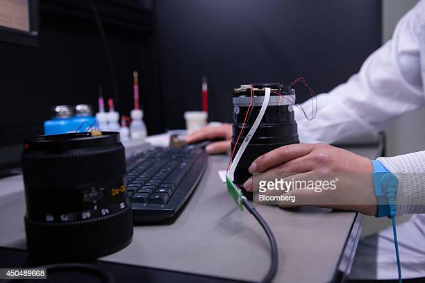 An employee uses a computer mouse during testing on Leica S camera lenses inside the Leica Camera AG factory as the company celebrates their 100th...