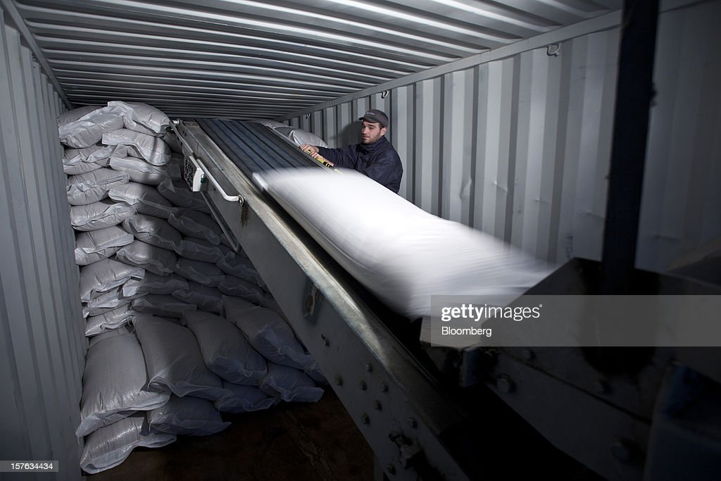 An employee uses a conveyor belt to load sacks of barley grain into a shipping container at the Groupe Soufflet plant in Nogent-sur-Seine, France, on Tuesday, Dec. 4, 2012. European Union corn imports may be the second-highest on record this season after drought parched crops and a surge in wheat exports curbed domestic grain supply. Photographer: Balint Porneczi/Bloomberg via Getty Images