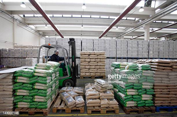 An employee uses a forklift truck to maneuver a pallet load of bagged rice inside the warehouse at Riso Scotti SpA's factory in Pavia Italy on Monday...