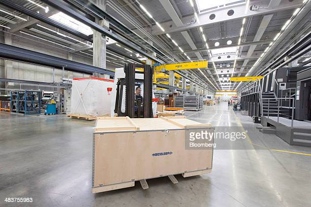 An employee uses a forklift truck to maneuver a section of a Heidelberg industrial printing press ahead of shipping at the Heidelberger...