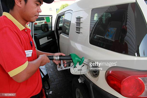 An employee uses a fuel pump to fill a customer's vehicle with unleaded petrol in Dubai United Arab Emirates on Monday July 4 2011 Abu Dhabi National...