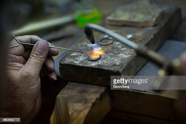 An employee uses a gas torch to manufacture a gold ring in the workshop for the Zolotos SA luxury jewelry store in Athens Greece on Monday July 13...