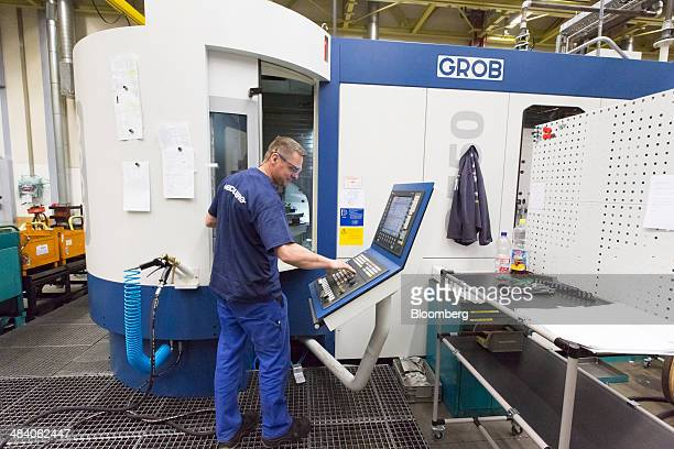 An employee uses a Grob G550 milling center manufactured by Grob Systems Inc in the Heidelberger Druckmaschinen industrial printing press...