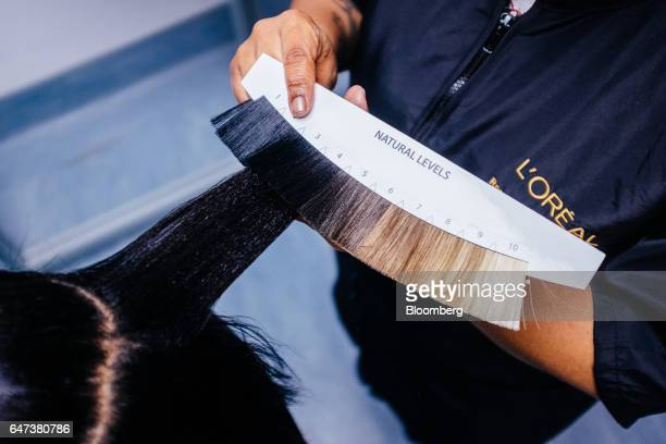 An employee uses a hair color swatch to match the hair color of a visitor in the research laboratory at the new L'Oreal SA Research and Innovation...