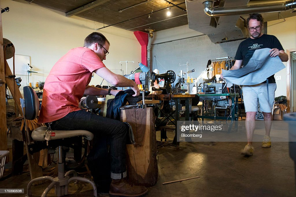 An employee uses a hammer and an anvil to hammer in copper rivets on a pair of denim jeans at Detroit Denim, in Detroit, Michigan, U.S., on Wednesday, June 12, 2013. The Commerce Department is scheduled to release monthly business inventories data on June 13. Photographer: Ty Wright/Bloomberg via Getty Images