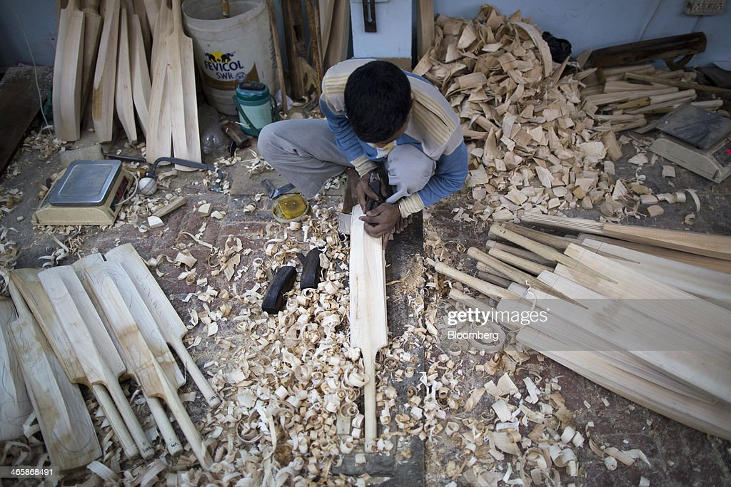 An employee uses a hand plane to shape a cricket bat at a Stanford Cricket Industries factory in Meerut, Uttar Pradesh, India, on Wednesday, Jan. 29, 2014. The Indian Premier League (IPL), the worlds richest cricket competition, auction for IPL 2014 is scheduled to begin on Feb. 12 with the seasons first match to be played on April 8. Photographer: Prashanth Vishwanathan/Bloomberg via Getty Images