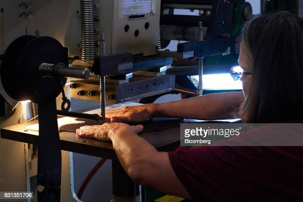 An employee uses a hot press to brand the leather of a ball glove at the Nokona manufacturing facility in Nocona Texas US on Thursday July 27 2017...