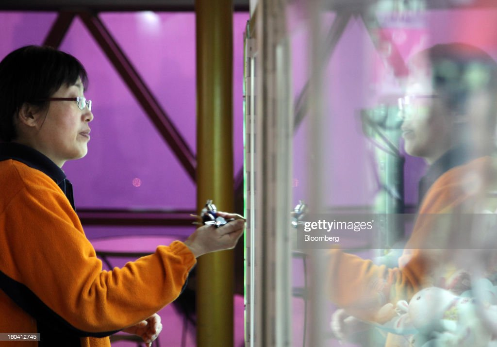An employee uses a key to open an arcade game machine inside the Oriental Pearl Tower in the Pudong area of Shanghai, China, on Wednesday, Jan. 30, 2013. China's economic growth accelerated for the first time in two years as government efforts to revive demand drove a rebound in industrial output, retail sales and the housing market. Photographer: Tomohiro Ohsumi/Bloomberg via Getty Images