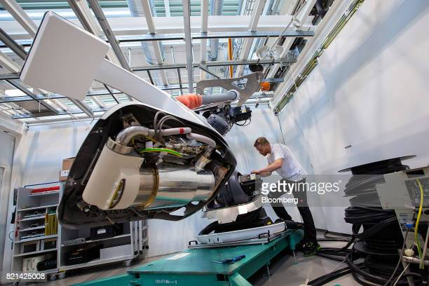An employee uses a Kuka AG robotic arm while working on the Xray detector of a Siemens Artis pheno angiography system on the assembly line at the...