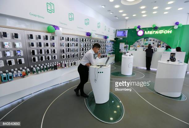 An employee uses a laptop computer inside a MegaFon PJSC mobile phone store in Moscow Russia on Tuesday Aug 29 2017 MegaFon considers various...