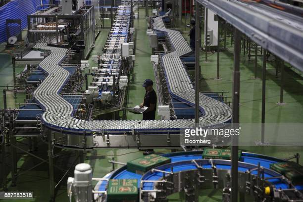 An employee uses a laptop computer while monitoring cans of Carabao energy drink moving along a conveyor on the production line at the Carabao Group...
