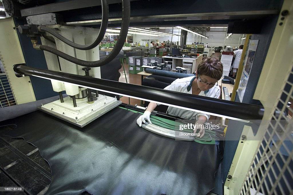 An employee uses a laser cutting machine to produce sections of leather during the production of Le Pliage Cuir bags at the Longchamp SAS workshop in Segre, France, on Monday, Sept. 9, 2013. Longchamp SAS, the French handbag maker, which is known for foldable Le Pliage nylon tote bags, expects sales in China to rise, Chief Executive Officer Jean Cassegrain said. Photographer: Balint Porneczi/Bloomberg via Getty Images