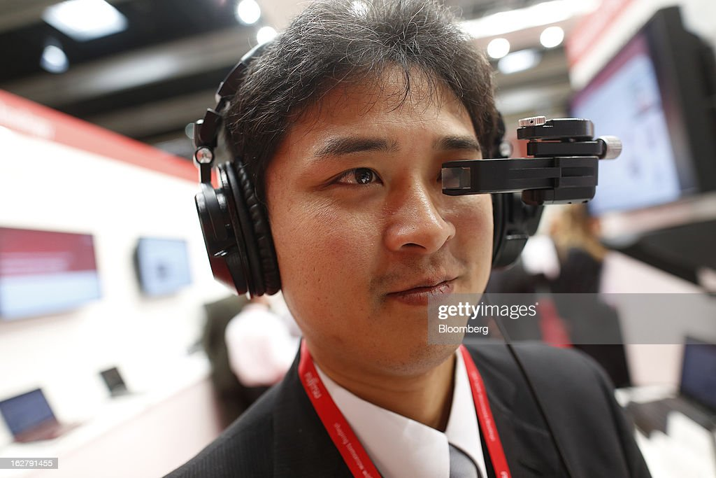 An employee uses a Laser Head Set (LHS) to test an audio-visual headphone system in the Fujitsu Ltd. pavilion at the Mobile World Congress in Barcelona, Spain, on Wednesday, Feb. 27, 2013. The Mobile World Congress, where 1,500 exhibitors converge to discuss the future of wireless communication, is a global showcase for the mobile technology industry and runs from Feb. 25 through Feb. 28. Photographer: Simon Dawson/Bloomberg via Getty Images