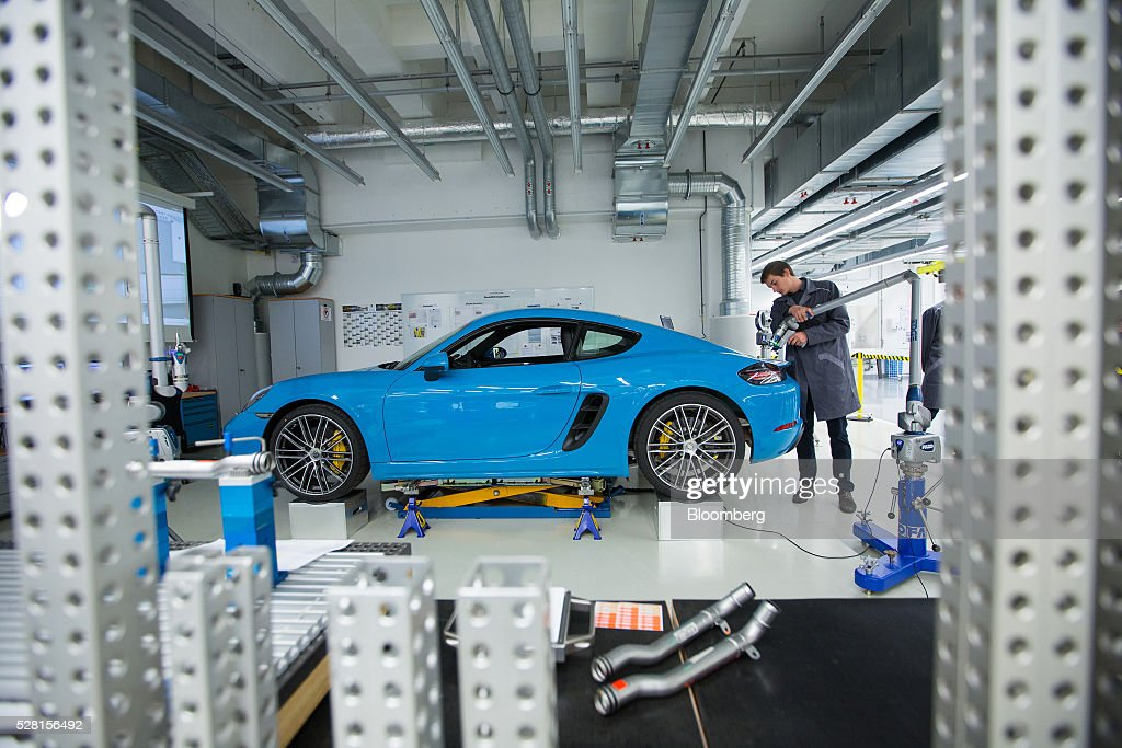 An employee uses a laser while taking measurements of a Porsche 718 Cayman luxury automobile during a quality control workshop at the automaker's headquarters in Stuttgart, Germany, on Wednesday, May 4, 2016. After the upscale Audi brand, Porsche is the second-largest earnings contributor at Volkswagen and generates the group's highest margins. Photographer: Krisztian Bocsi/Bloomberg via Getty Images