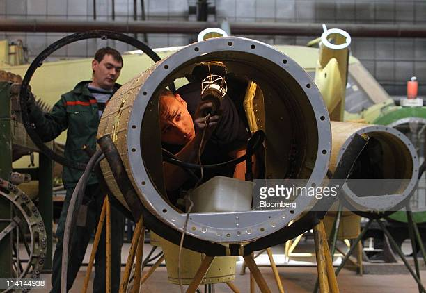 An employee uses a light to inspect the interior of a Mi17 helicopter section in the intermediate assembly shop at the JSC Kazan Helicopters factory...