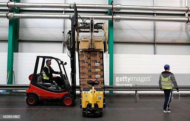 An employee uses a Linde AG forklift to load a stack of boxed Fyffes bananas onto a pallet truck at Fyffes Plc's ripening and fruit distribution...