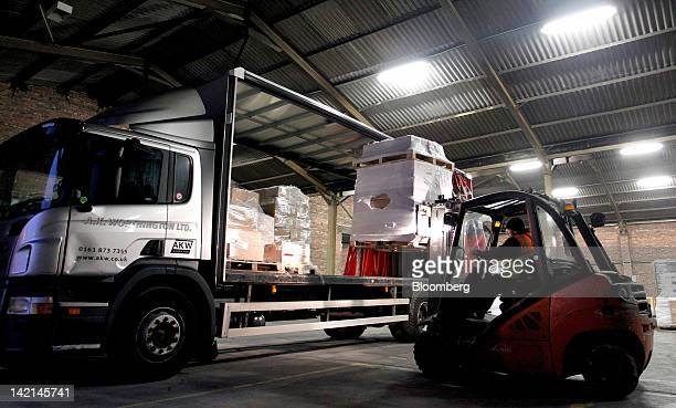 An employee uses a Linde AG forklift truck to load pallets of goods into a road haulage truck at AKW Group Plc's freight distribution depot in...