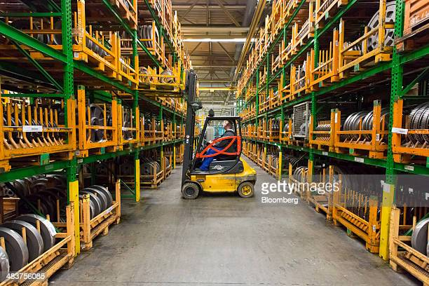 An employee uses a Linde AG forklift truck to maneuver a pallet onto printing press component storage racks in the Heidelberger Druckmaschinen AG...