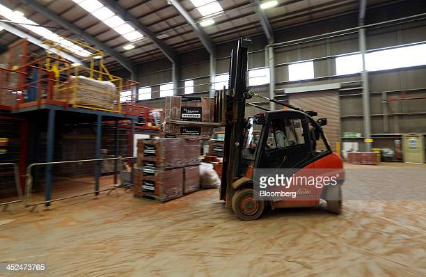 An employee uses a Linde AG forklift truck to maneuver a wrapped pallet of newly manufactured Ecostock house building bricks at Hanson Brickworks...