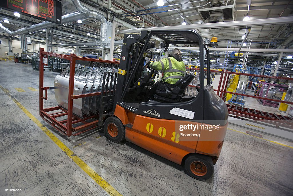 An employee uses a Linde AG forklift truck to move a pallet of automobile doors through Jaguar Land Rover Plc's assembly plant, a unit of Tata Motors Ltd., in Halewood, U.K., on Wednesday, Feb. 13, 2013. Carmakers from Ford Motor Co. to Audi AG and Jaguar Land Rover Plc are using record amounts of aluminium to replace heavier steel, providing relief to producers of the metal confronting excess supplies and depressed prices. Photographer: Simon Dawson/Bloomberg via Getty Images