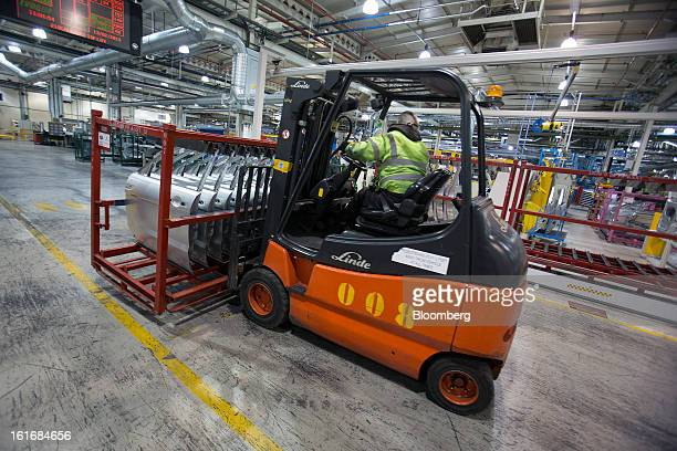 An employee uses a Linde AG forklift truck to move a pallet of automobile doors through Jaguar Land Rover Plc's assembly plant a unit of Tata Motors...