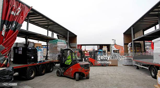 An employee uses a Linde AG forklift truck to unload pallets from one road haulage truck and reload into another at AKW Group Plc's freight...