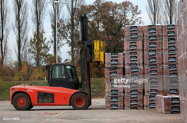 An employee uses a Linde AG front loader to maneuver a wrapped pallet of newly manufactured Ecostock house building bricks in the yard at Hanson...