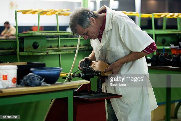 An employee uses a machine to polish the leather sole of a luxury shoe at the Always Shoes SA factory in Felgueiras Portugal on Wednesday Dec 18 2013...